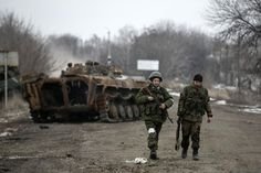 Fighters with the separatist self-proclaimed Donetsk People's Republic army walk by a destroyed Ukrainian armoured personnel carrier at a check point on the road from the town of Vuhlehirsk to Debaltseve, February 20, 2015. REUTERS/Baz Ratner