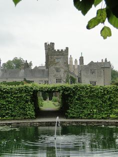 Levens Hall Gardens, Cumbria, England across a pond and looking set for a story