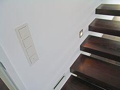 Auf diesem Bild sieht man die freitragenden Treppe, die Treppenspots und die GIRA E22 Schalterserie mit gerade stehenden Schaltwippen.