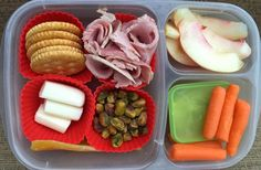 Healthy and easy lunch box idea!  Crackers, cheese, ham, pistachios, dried mango, nectarine, carrots, hummus