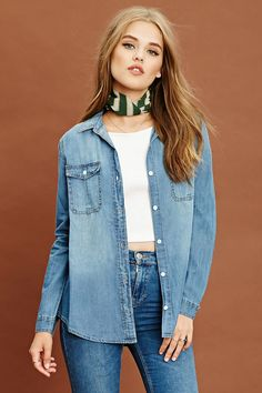 A woven chambray shirt featuring a basic collar, two front button pockets, a button front, long sleeves with button cuffs, and a slightly curved hem.