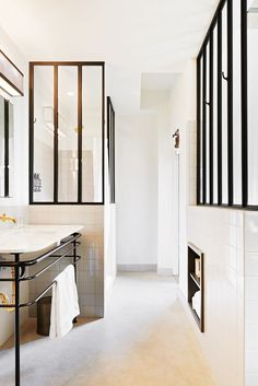 All-white bathroom with framed glass walls, white tile, and an industrial vanity sink