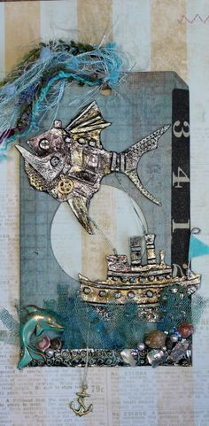 Sail Fish.  Lots of embossed metal tape tinted with alcohol ink, and built up to create the fish and ship.  Some shells, an anchor, and sea colored netting add to the ocean feel.  Theme: Steampunk and Lace for Roses on my Table tag swap.
