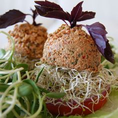 Raw Vegan Walnut Burger with avocado, clover and sunflower sprouts in a tomato bun.