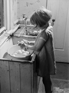 Little girl washing the eggs she just gathered.  Judging by the haircut, I'd say this is in the 1930's.