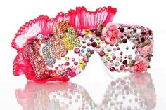 This Couture eyewear is embellished with multi-colored Swarovski crystals, pink rosettes, a multi-colored crystallized Barbie medallion, and trimmed in Hot Pink pleated organza with a gingham bow. The sides are covered in Gold crystallized studs, and more crystals. ALL Jaesyn Burke eyewear comes with a matching drawstring bag. Please allow 3-4 weeks for delivery. REGULAR PRICE: 250.00, SALE PRICE: 200.00