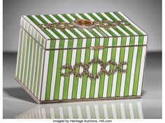 A Fabergé Silver, 14k Gold, Enamel, and Diamond Combination Cigarette and Match Safe Case Inset with Gold Poltina Coin, St. Petersburg, Russia, circa 1908-1917. The rectangular hinged case with a striped ground articulated in gold of alternating bands of green guilloché enamel and white enamel, with applied gold laurel leaf swags, the center set with a gold ruble showing Elizabeth the Great within a border of rose-cut diamonds, match strikes to underside and interior lid.