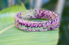 Oregon-based artist Sarah Smith, owner of Etsy store Modern Flower Child, creates hand-made resin bracelets, bangles and earrings using pla. Resin Bracelet, Resin Ring, Resin Jewelry, Jewellery, Resin Flowers, Tiny Flowers, Dried Flowers, Kids Jewelry, Jewelry Making