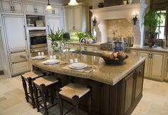 A white kitchen featuring a dark island and breakfast bar. What do you think of the stove backsplash?