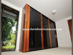 Built under a Darwin hi set home this set of Infinity sliding doors was constructed to compliment existing furnishings and add a touch of luxury. The timber is Merbau and the solid end panel was constructed to accommodate a the future placement of a small television on a swinging bracket (note the powerpoint at the top LHS)  https://www.formfunctionnt.com.au/