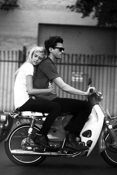 A black and white photograph of a couple on a motorbike.