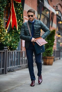 Make a dark green quilted bomber jacket and dark blue trousers your outfit choice for a sharp, fashionable look. Want to go easy on the shoe front? choose a pair of dark red leather desert boots for the day. Shop this look for $295: http://lookastic.com/men/looks/sunglasses-long-sleeve-shirt-cable-sweater-bomber-jacket-messenger-bag-dress-pants-desert-boots/7342 — Dark Brown Sunglasses — Light Blue Long Sleeve Shirt — Navy Cable Sweater — Dark Green Quilted Bomber Jacket — Brown ...