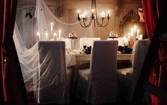 Dining table decorated for Halloween with tulle textiles, candles and accessories.