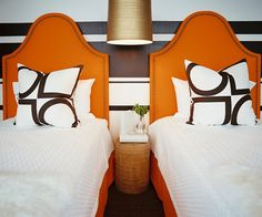 Wall Treatment - A pair of twin beds with orange headboards in front of a striped wall