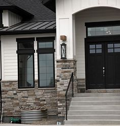 Modern rustic white farmhouse. Black doors. Black trim. Stone, board and baton and siding. Black metal roof. Black garage doors.