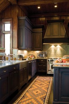 Granite countertops, a stainless steel apron sink and a brightly coloured rug add character.    The cabinetry's dark finish contributes to the lodge theme of Grammy-winning saxophonist Kenny G's home. A pale green ceramic tile backsplash features accent tiles with subtle pinecone and leaf motifs.