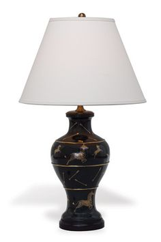 Elegant and iconic Scalamandre Maison Le Zebre Lamp Black will enhance your home decor in a sophisticated, classic style. The chase of the Le Zebre is playfully shown on the porcelain lamp with accents of hunting arrows missing the zebre. Inspired by Scalamandre's iconic wallpaper from New York City's late lamented restaurant Gino's.