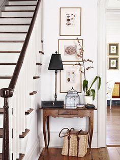 The couple found the spindles, newel post, and banister of their new staircase in the offices of a local preservation organization. Tere decorated the hall with a high-low mix: A custom tiger-maple table pairs with bargains like a terrarium from T.J. Maxx and artwork scored on eBay.