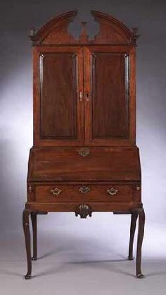 An American Federal bureau bookcase,  the top with broken arch pediment centred by a finial, above two panelled cupboard doors, enclosing an adjustable shelf and drawers, the rectangular fall-flap enclosing a fitted interior, above a long drawer and apron centred by a carved shell, on cabriole legs with pad feet 98cm wide, 222cm high, 59cm deep -    Sold for £21,150