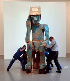 Technicians install a sculpture by German artist Georg Baselitz at the Paris Museum of Modern Art today. A retrospective of his sculpture opens in two days. While Baselitz began his career as a painter and engraver, the exhibit features almost all of his sculptural work, created over a period of more than thirty years.     Photo by Jacques Demarthon/ AFP/ Getty Images.