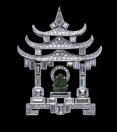 Platinum diamond and emerald brooch of a shrine. The architecture, which is entirely carried out in diamonds of various cuts - circular, emerald, baton - culminating in the trapezoid shaped stones at the apex of the roof, encloses a carved emerald Buddhist divinity raised up on steps. C.1927.