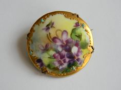 This fabulous vintage brooch is just beautiful. It is a hand painted design of rich purple violets with exquisite coloring and fine detail. A metallic gold border with with turquoise painted stones appear as if set into the frame. The painted porcelain disc is set into a brass frame with original vintage pin findings. The brooch is in excellent condition with no virtually no wear, scratches or chips. The brooch measures 1 1/2 across and is slighted domed. It is just lovely and perfect for…