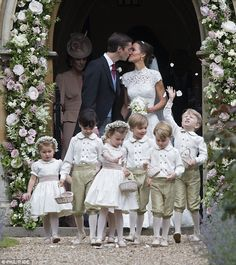 Newlyweds: James and Pippa shared a kiss under the floral archway at the church entrance...