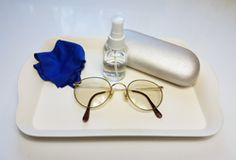 Care Of Self: Cleaning spectacles with a water spray and polishing cloth