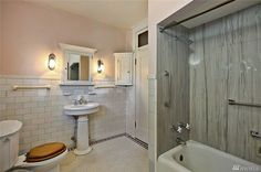 Like the transom window, corner cabinet, towel bars. Wall tile looks wrong (newer?) and tub surround and oak toilet seat must go. 1906 Capitol Hill home, 955 16th ave E.