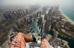 'I'm ok, I'll just sit here a minute...' RUSSIAN daredevil standing on top of a Dubai skyscraper. Nineteen-year-old Alexander Remnev...