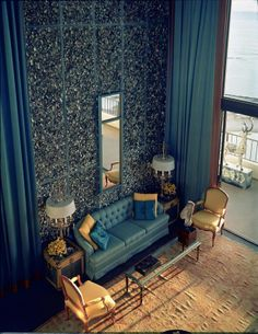 This room has high walls that have been covered in metallic rocks. The wall has then been lined with tall blue curtains. The room has a very open feel to it.