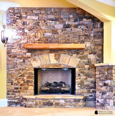 Full height ventless fireplace made of dry stacked natural Tennessee Field Stone with a rough cut Cedar mantle. By White Oak Renovations