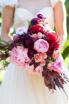 Pink, peach and red wedding bouquet with peonies and ranunculus