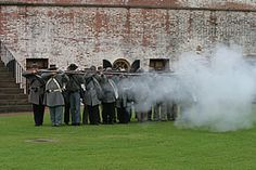I love Fort Macon, in Atlantic Beach, NC  Image of a group of men dressed in confederate           uniforms firing muskets.