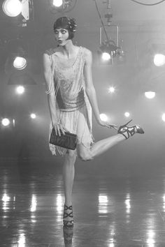 The light on this photo illuminates the flapper girl dancer. She is on stage and she has a cheeky expression. She might be posing for a photo or performing an act to get a part in a theatre.