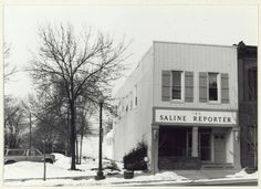 . Saline Reporter, 106 W. Michigan Ave. Constructed circa 1870. Masonry two story commercial building with recessed entry framed by wooden pilasters. The second story is covered with vertical aluminum siding and wooden shuttered windows. Full signage separates the first and second story. Beside double front entry doors is a small wooden door which probably leads to the second level. A line of second story windows fenestrates the west facade. In the 1870\'s this building housed a hardware…