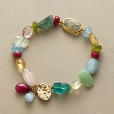 ELIANA BRACELET -- Multi hued gemstone nuggets of aqua, apatie, citrine, ruby, rose quartz, peridot and prehnite guide the eye to a centerpiece aquamarine wrapped in 24kt gold. Handmade by Nava Zahavi exclusively for Sundance. 14kt gold clasp. Approx. 7-1/4L.