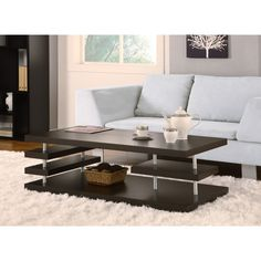 With its sleek, modern design, this striking coffee table is the perfect fit for a contemporary space. The table is crafted with shining silver posts and an unusual, multi-tiered design that creates additional surfaces for storage and display.