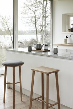 OCCASIONS 2017. Light kitchen with a view. The oak stools add a clean look to the beautiful light kitchen.