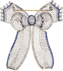 "Diamond, Sapphire, Gold Brooch The openwork bow brooch features European, full and single-cut diamonds weighting a total of approximately 1.45 carats, enhanced by French-cut sapphires weighing a total of approximately 1.30 carats, set in 18k white gold, completed by a pinstem and ""C"" catch on the reverse. Gross weight 19.65 grams."