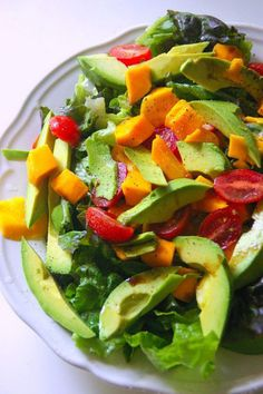 Mango, avocado and sweet cherry tomatoes with mixed greens