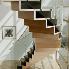 A range of stairs using interlocking timber shapes as treads and performing a structural element. Glass forms the balustrade on this striking collection.