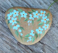 I love rocks. I collect rocks. So why not paint rocks? :-)    This is a heart shaped rock, with forget me not design.    It is sealed with several