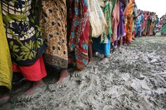 Bangladeshi women stand in a queue to receive relief material at the cyclone affected village of Nowabanki, Bangladesh, Friday, May 29, 2009.