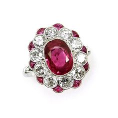 Early 20th century ruby and diamond cluster ring, French c.1915,  of shaped oval outline, the cushion cut ruby bordered by brilliant cut diamonds and with outer calibrй cut ruby highlights, millegrain set in platinum, rubbed serial number possibly 26690