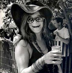 Janis Joplin smiling with a beer can in hand
