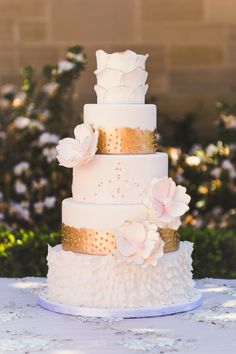 Gold and white layered wedding cake with fondant flowers and peridots #gold #goldwedding #weddingcake #goldweddingcake #cake