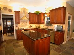 Tumbled travertine with slate accents, to coordinate with the slate floor (kitchen by Bay Area Kitchens)