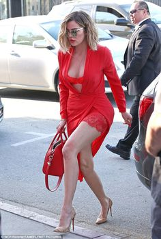 Modelesque:The reality star looked ravishing in red as she rocked a peek-a-boo wrap around an exposed brassiere and thigh-hugging knickers