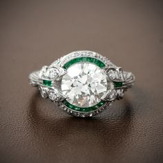A gorgeous and fine Art Deco Engagement Ring with an emerald halo and bow motif filigree. Sold by Estate Diamond Jewelry.